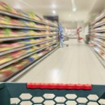 Shopping concept in supermarket for fast consumer lifestyle. Shopping cart in in blurred motion through the aisles.